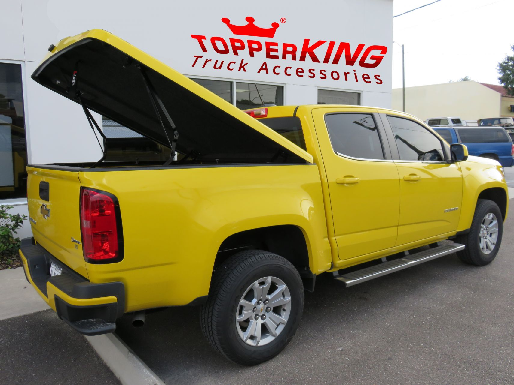 Bright yellow Chevy Colorado with a LEER 700 hard tonneau and running boards by TopperKING in Brandon, FL 813-689-2449 Call today to start on your truck!