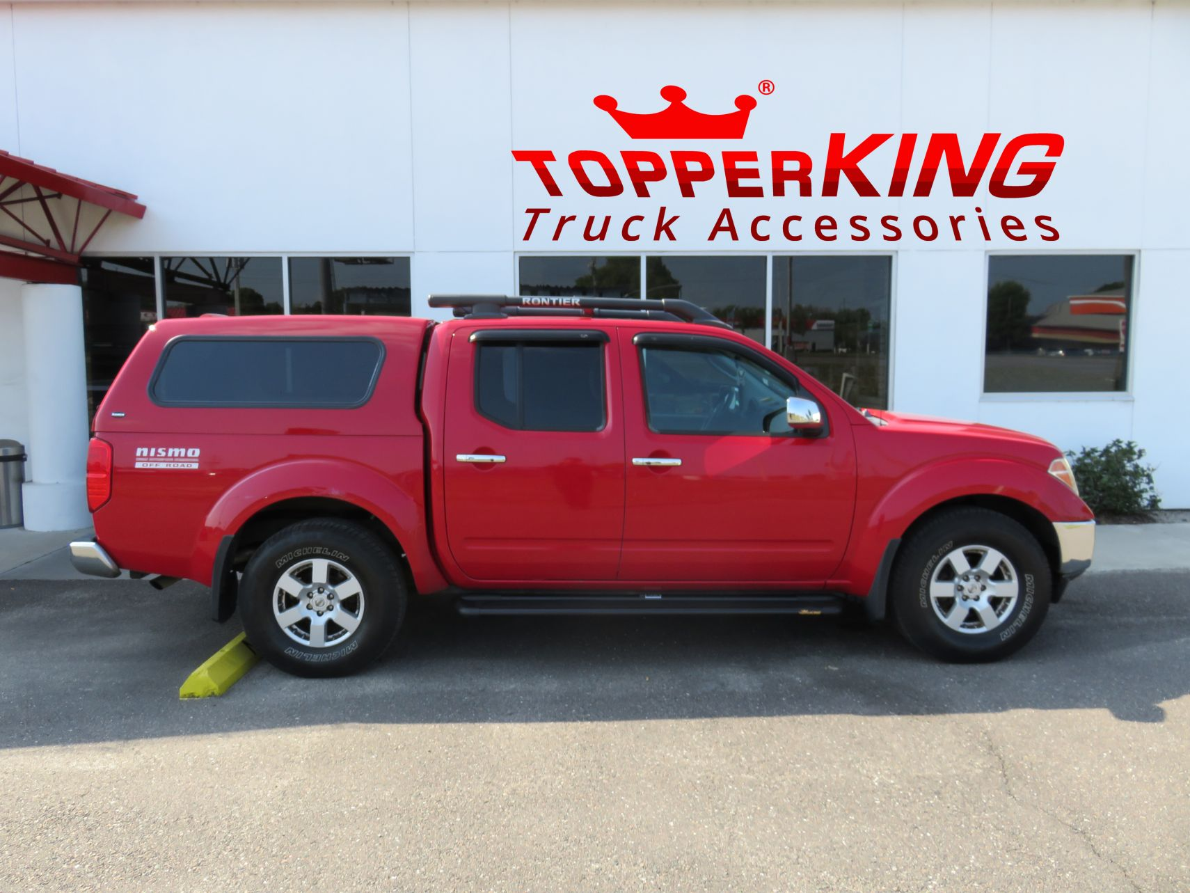 2014 Red Nissan Frontier with a Ranch Echo fiberglass topper, a custom hitch, blacked out nerf bars, and roof racks by TopperKING in Brandon, FL 813-689-2449 Call today to start on your truck!