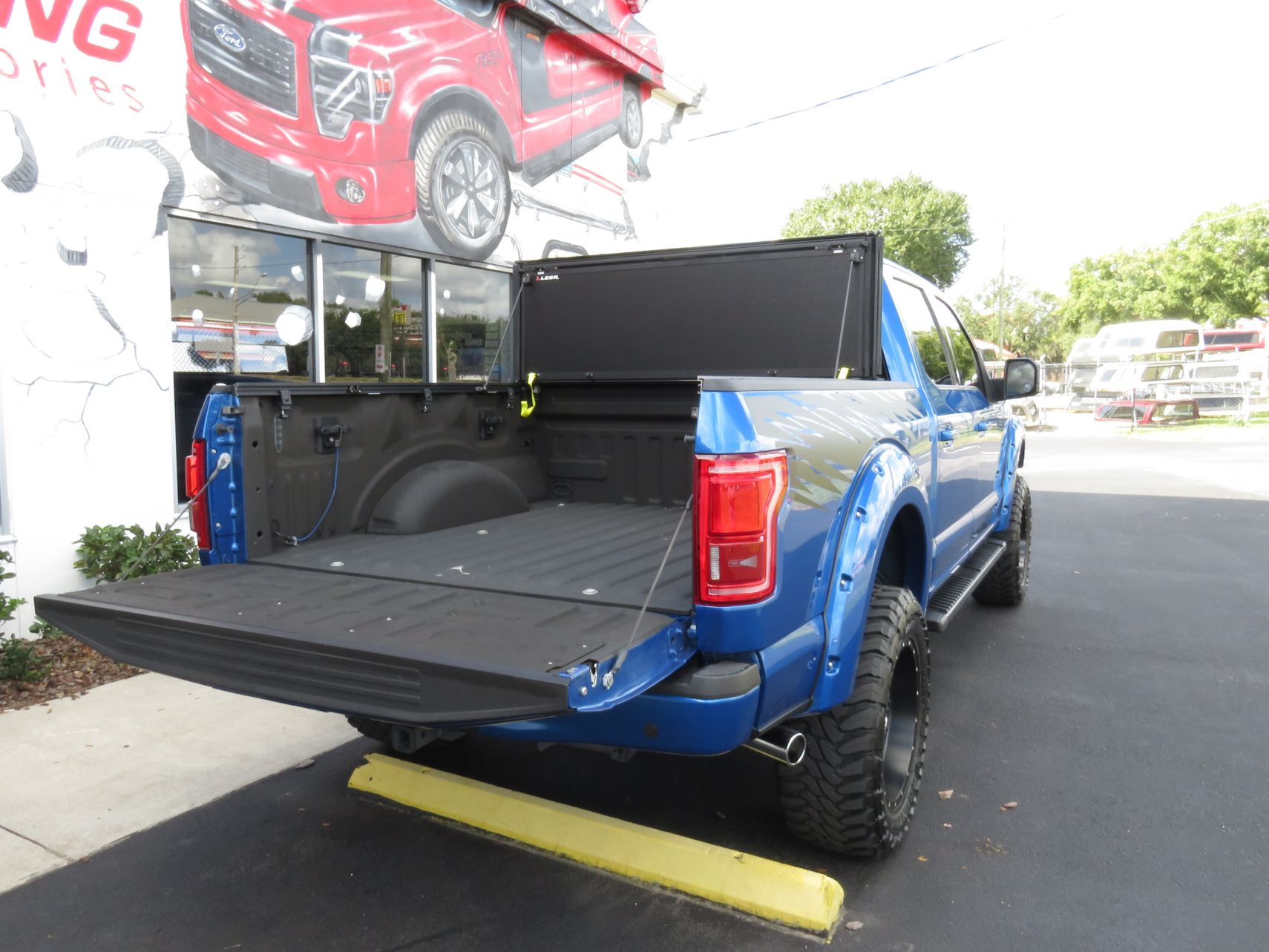 2015 Blue Ford F150 LEER 350M, Bull Bars, Custom Hitch. and more by TopperKING in Brandon, FL 813-689-2449 or Clearwater, FL 727-530-9066. Call today!