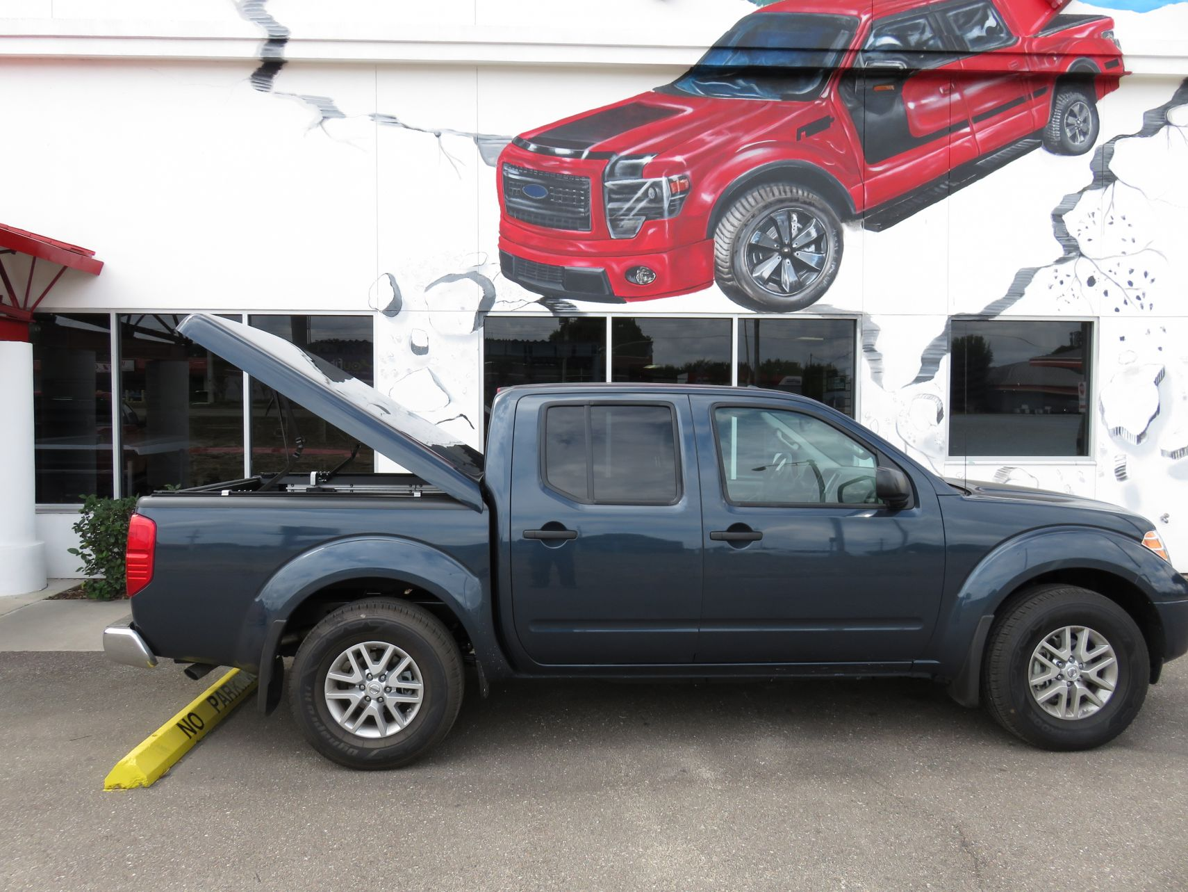 2015 Nissan Frontier with a brand new Ranch SportWrap fiberglass lid and a custom hitch by TopperKING in Brandon, FL 813-689-2449 Call today to start on your truck!