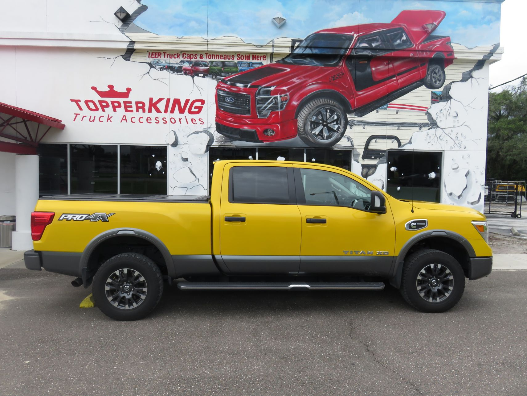 2017 Yellow Nissan Titan with a Leer Trilogy X2T folding tonneau cover, a custom hitch, running boards, and tint by TopperKING in Brandon, FL 813-689-2449 Call today to start on your truck!