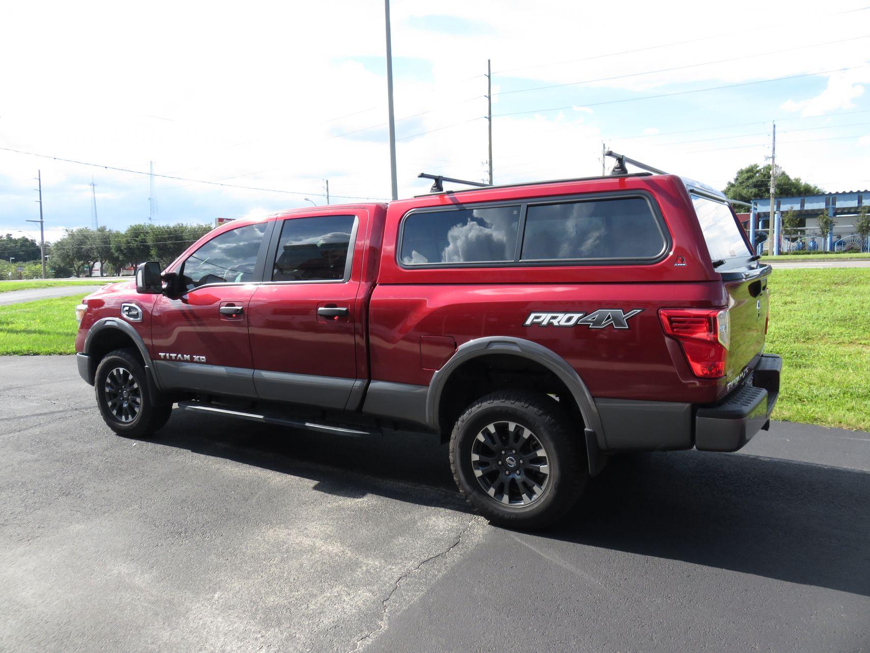 2018 Red Nissan Titan XD Leer 100R Roof Racks, Custom Hitch, Nerf Bars, Tint by TopperKING in Brandon, FL 813-689-2449 or Clearwater, FL 727-530-9066.