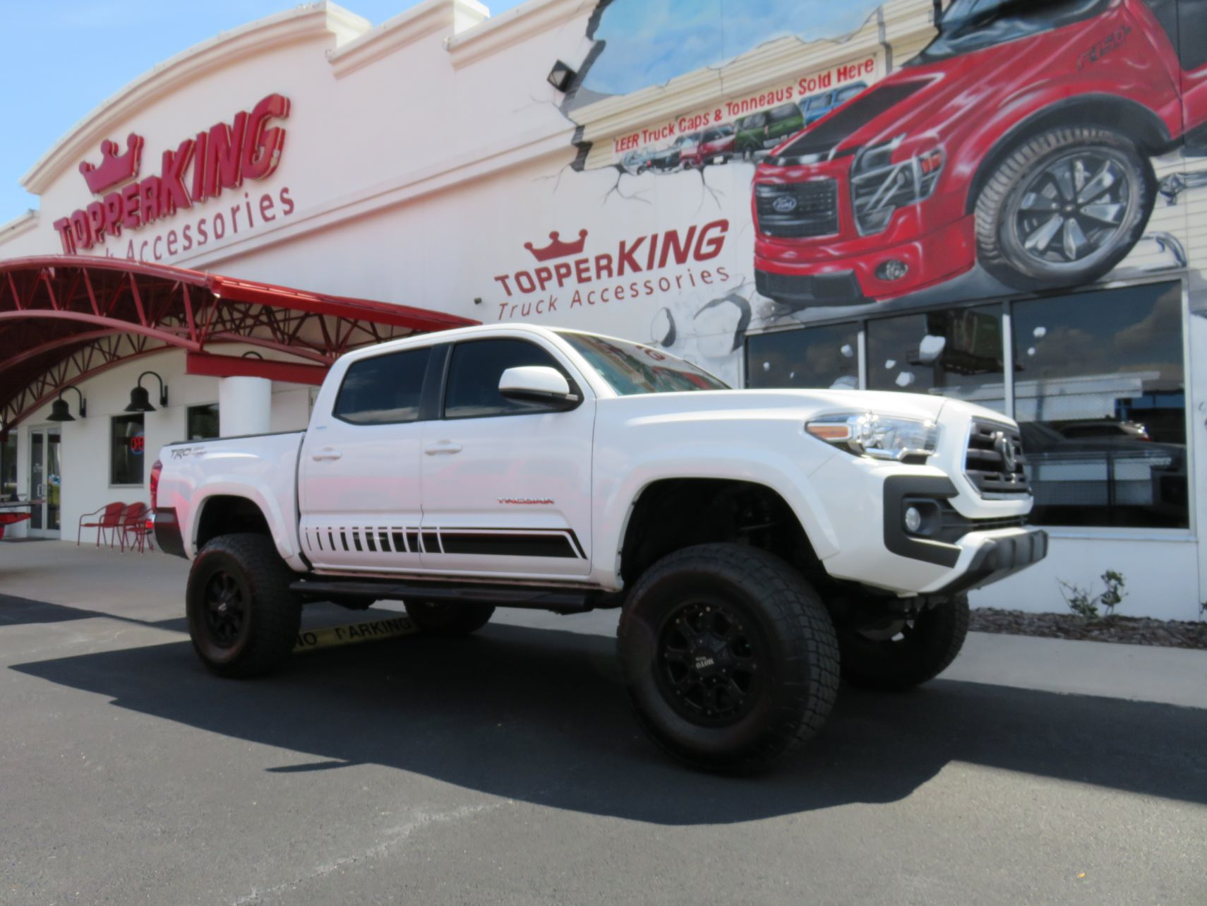2019 Toyota Tacoma with LEER 350M, Nerf Bars, Hitch, Graphics, Bedliner by TopperKING in Brandon, FL 813-689-2449 or Clearwater FL 727-530-9066. Call today!