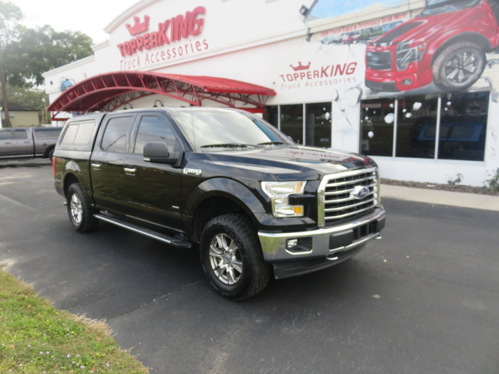 2019 Black Ford F150 with LEER 100XR, Nerf Bars, Tint, and Hitch by TopperKING in Brandon, FL 813-689-2449 or Clearwater, FL 727-530-9066. Call today!