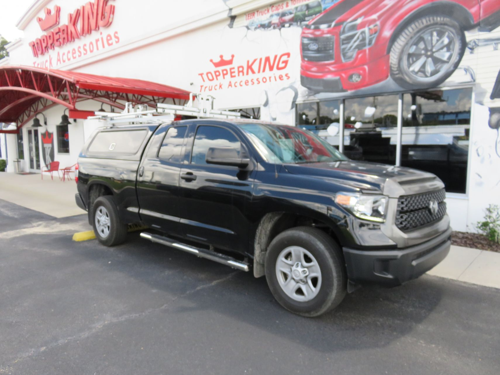 2018 Toyota Tundra with LEER 100RCC, Roof Racks, Side Access, Nerf Bars, Hitch by TopperKING Brandon 813-689-2449 or Clearwater 727-530-9066.